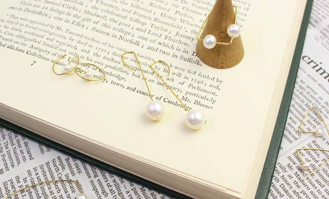 洋書の上にMelissa McArthur Jewellery 淡水パール ピアス ストレートドロップやリングが並べられている画像