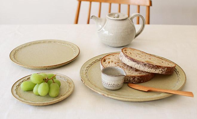 萩原千春(はぎはらちはる)+S しのぎリムプレート シュガーグリーンがパンやフルーツと共に食卓に並んでいるところ