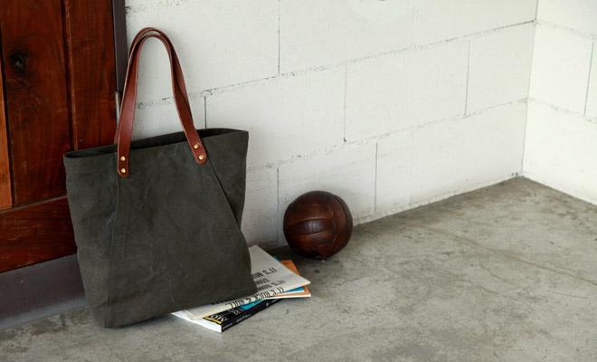 RHYTHMOS リュトモス College トートバッグが雑誌などと共に部屋の片隅に置かれている画像