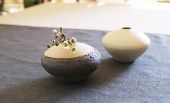 藤居奈菜江 ふじいななえ 練り込み 花入れ 黒に花が活けられ卓上に飾られている画像
