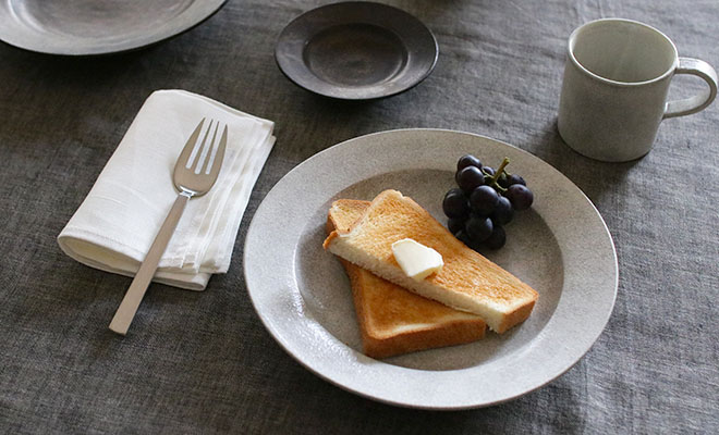 パンとフルーツを盛られた戸塚佳奈 とづかかな リムプレート 25cmが食卓に並べられている画像
